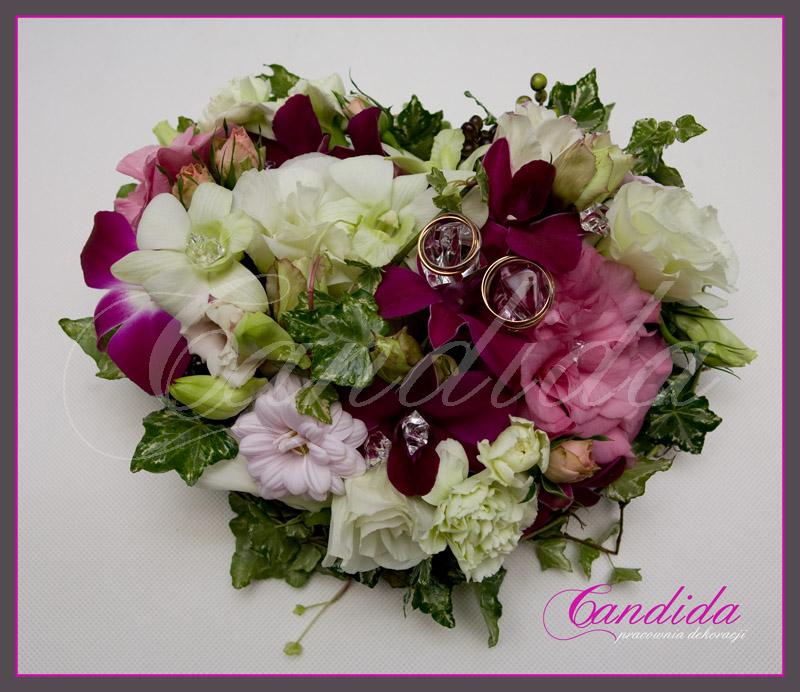 kwiatowa poduszka na obrączki  w formie serca wykonana z pistacjowej i różowej eustomy, storczyka dendrobium, goździka i margerytki