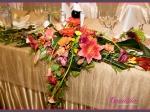 Dekoracja stołu Młodej Pary wykonana z pomarańczowych i czerwonych gerber, cantedeskii, czerwonych lilii, żółtych frezji, craspedii