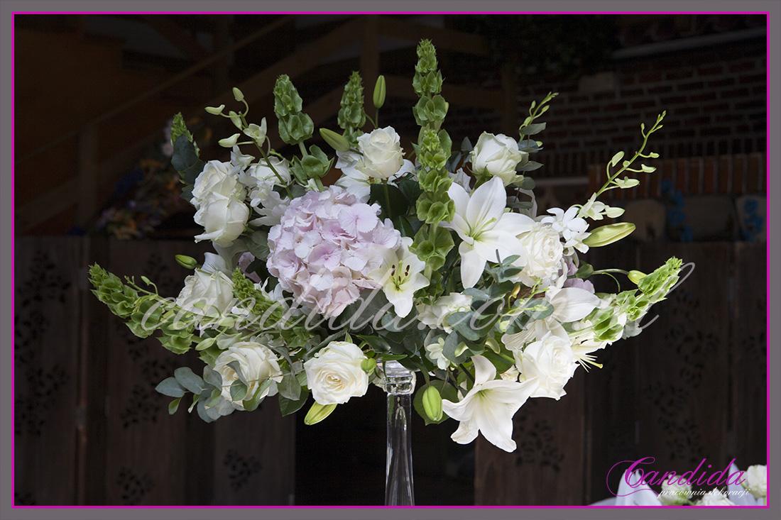 wesele w hotelu Boss, kompozycja kwiatowa w wysokim naczyniu szklanym na stół weselny, dekoracje weselne w hotelu Boss, dekoracje sali weselnej, dekoracje stołów weselnych