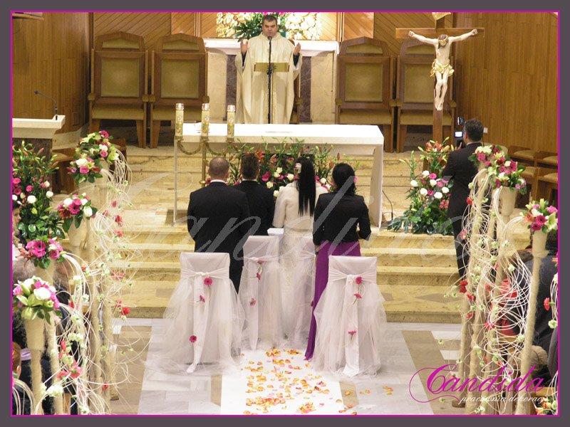Dekoracja kościoła, nawy głównej. Do dekoracji użyto tuby z kwiatami i zwisającym rattanem. Biały dywan ozdabiają płatki róż.