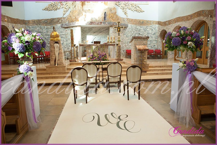 dekoracja ślubna kościoła biały dywan z inicjałami Pary Młodej, kompozycje kwiatowe na postumentach