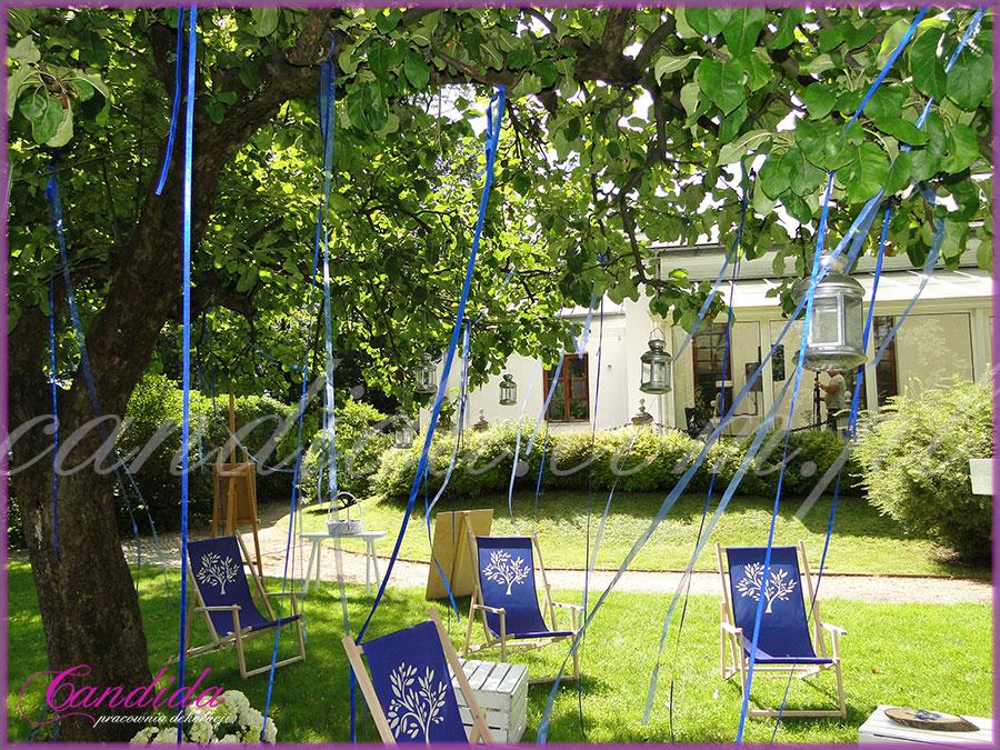 strefa chillout na weselu, drzewo przyozdobione wstążkami i latarenkami, leżaki dla gości ozdobione motywem przewodnim, dekoracje kwiatowe  ślubu w plenerze w Dworze Radzin 26