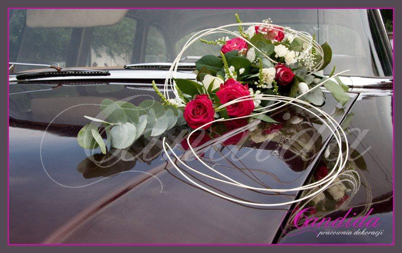 Dekoracja maski samochodu w formie wydłużonej kompozycji wykonanej z czerwonych róż z eukaliptusem