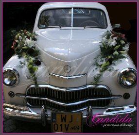 Dekoracja maski samochodu w formie 2 wydłużonych kompozycji wykonanych z białych lilii, białego storczyka