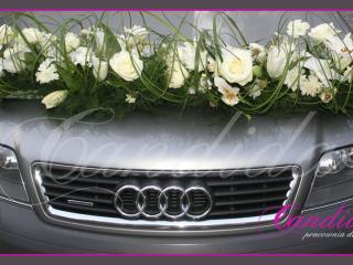 Dekoracja samochodu w formie kompozycji złożonej z lilii, scabiozy, mieczyków, traw ozdobnych, frezji