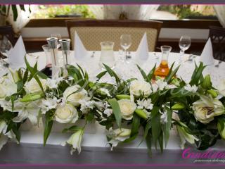 Dekoracja stołu Młodej Pary wykonana z białych róż, białych mieczyków,  białych lilii, białej frezji