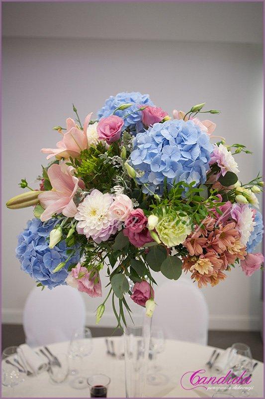 kompozycja kwiatowa na wysokim naczyniu szklanym, dekoracje sali weselnej w hotelu Brant
