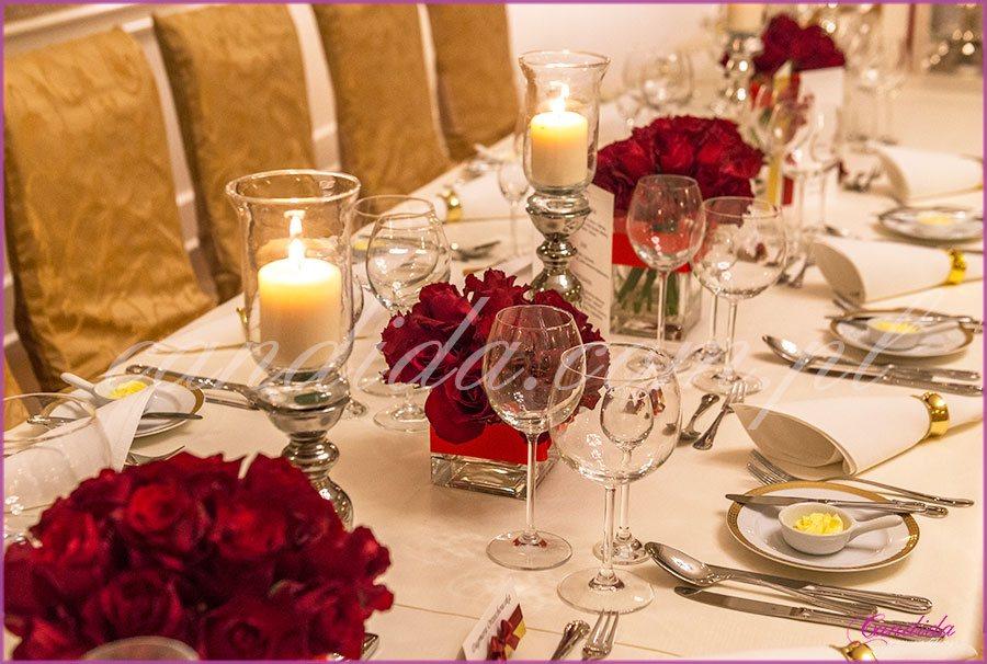 dekoracja weselna w restauracji Pod Gigantami kompozycje kwiatowe z róż w niskich naczyniach i świeczniki dekoracja stołu Młodej Pary